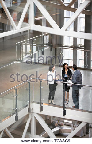 Business people talking on office atrium balcony - Stock Photo