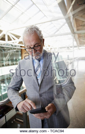 Senior businessman using smart phone on office atrium balcony - Stock Photo
