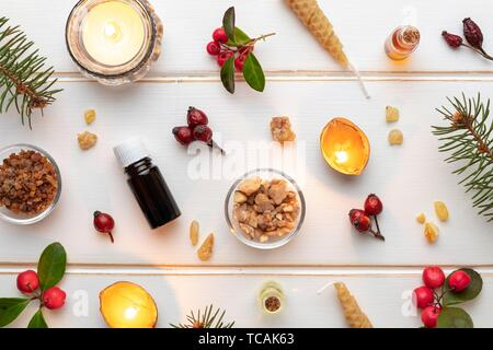 Bottles of essential oil on a white Christmas background with frankincense, myrrh, wintergreen and candles made from nut shells. - Stock Photo
