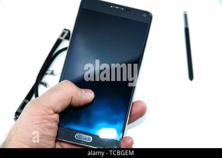 man finger touch on big smart phone with smart pen pen in hands isolated on the white background and with eye glasses. - Stock Photo
