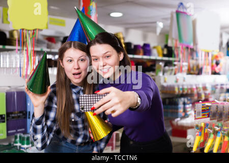 Comically dressed happy girls making funny selfies photo in festive accessories shop - Stock Photo