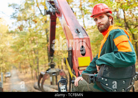 Forest farmer as a crane operator on the forwarder during logging in the wood harvest - Stock Photo