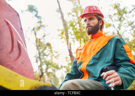 Forest worker as a crane operator on the forwarder while chopping wood or loading - Stock Photo