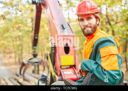 Smiling crane operator in logging on the forest crane of Forwarder in the woods - Stock Photo