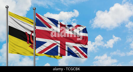 Brunei and United Kingdom flag waving in the wind against white cloudy blue sky together. Diplomacy concept, international relations. - Stock Photo