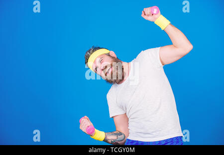Motivated athlete guy. Sportsman training with dumbbells blue background. Improve your muscles. Use weights or dumbbells. Man bearded athlete exercising dumbbell. Athlete training with tiny dumbbell. - Stock Photo
