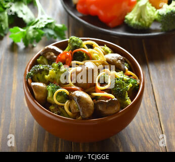 Egg noodles with vegetables in bowl on wooden table - Stock Photo