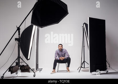 Professional photography studio showing behind the scenes lights. fashion handsome young man model at studio in the light flashes, sitting and looking - Stock Photo