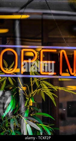 Panorama Close up of a neon open sign hanging on the glass wall of a commercial building - Stock Photo