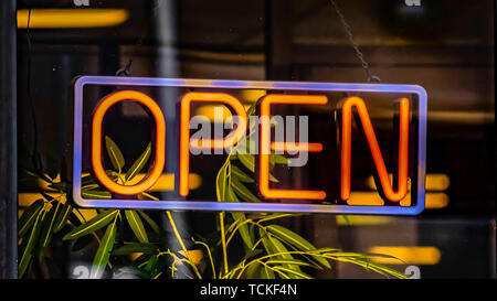 Panorama frame Close up of a neon open sign hanging on the glass wall of a commercial building - Stock Photo