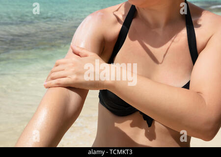 Close-up Of A Woman Applying Sunscreen Lotion On Her Arm At Beach - Stock Photo