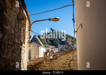 Ancient alley in Pietrapertosa village. In the background, Dolomites of Basilicata mountains called Dolomiti Lucane.  Basilicata region, Italy - Stock Photo