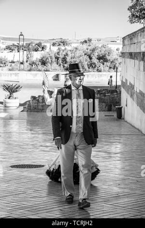 CORDOBA, SPAIN - MAY 30, 2019: A senior dressed couple at Feria de Cordoba, Feria de Nuestra Senora de la Salud or Cordoba Fair, black and white photo - Stock Photo