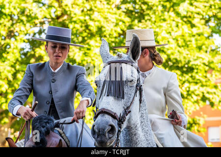 CORDOBA, SPAIN - MAY 30, 2019: Two female horse riders at Feria de Cordoba, Feria de Nuestra Senora de la Salud or Cordoba Fair - Stock Photo