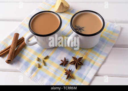 Indian traditional Masala chai tea in a mugs and kitchen herbs, over white table background with copy space for text. - Stock Photo