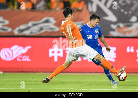 English-born Taiwanese football player Tim Chow, right, of Henan Jianye challenges a player of Wuhan Zall in their 4th round match during the 2019 Chinese Football Association Super League (CSL) in Wuhan city, central China's Hubei province, 8 June 2019.  Wuhan Zall played draw to Henan Jianye 0-0. - Stock Photo