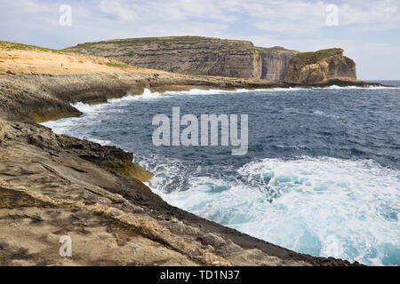 Scenic view of cliffs, fungus rock and blue ocean at dweira bay in gozo, malta. - Stock Photo