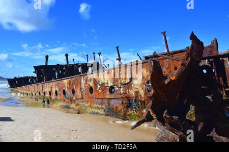 The rusty wreck of the vessel Maheno on the shores of Fraser Island (Queensland, Australia). The antique rusty and damaged boat and corrosion in the o - Stock Photo