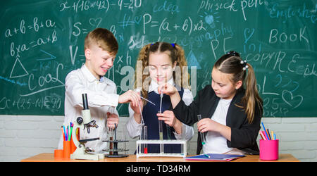 Group school pupils study chemistry in school. Boy and girls enjoy chemical experiment. Organic chemistry is study of compounds containing carbon. Basic chemical reactions. Fascinating chemistry. - Stock Photo