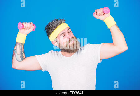 Athlete training with tiny dumbbell. Motivated athlete guy. Sportsman training with dumbbells blue background. Improve your muscles. Man bearded athlete exercising dumbbell. Use weights or dumbbells. - Stock Photo