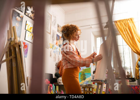 Wearing squared shirt. Red-haired young artist wearing squared shirt painting on canvas in workshop - Stock Photo