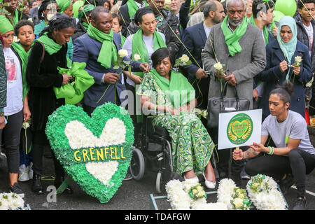 North Kensington, West London. UK 14 Jun 2019 - Survivors, family and friends of the victims wear symbolic green scarf to commemorate the second anniversary of the Grenfell Tower fire. On 14 June 2017, just before 1:00Êam a fire broke out in the kitchen of the fourth floor flat at the 24-storey residential tower block in North Kensington, West London, which took the lives of 72 people. More than 70 others were injured and 223 people escaped.   Credit: Dinendra Haria/Alamy Live News - Stock Photo