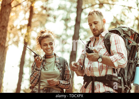 Everything is great. Joyful active couple speaking on walkie talkies while hiking together - Stock Photo