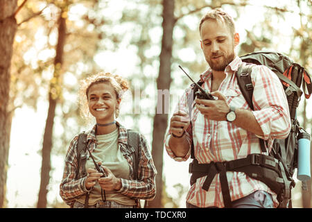 Electronic devices. Delighted cheerful couple using special walkie talkies while hiking together - Stock Photo