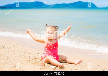 cute baby girl on the seashore sits on the sand and builds a castle on a background of waves.  - Stock Photo