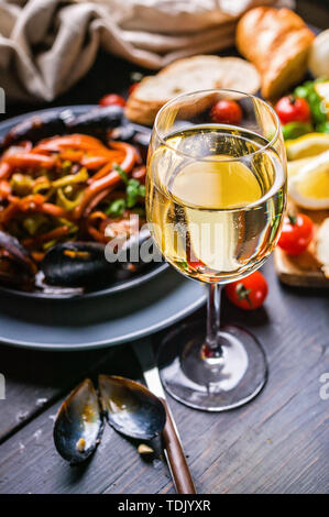 A glass of dry white wine on the background of Italian cuisine. Pasta, mussels and wine. - Stock Photo