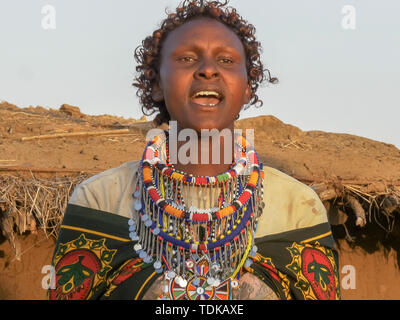 close up of a maasai woman in green singing at enkereri village near masai mara in kenya - Stock Photo