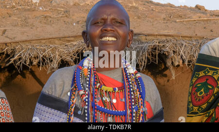 close up of a maasai woman wearing grey clothing and traditional jewellery singing in a village near masai mara in kenya - Stock Photo