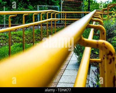 View on a rusty yellow railing of a sidewalk on a sunny day. - Stock Photo