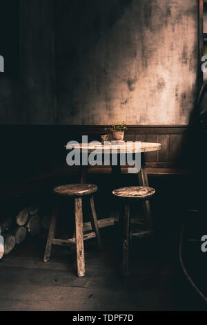 Dramatic photo a woodent table and chairs in a corner of a English Pub - Stock Photo