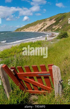 red pasture gate at the northeast coast of Samsoe Island in summer, Kattegat, Denmark, Samsoe, Maarup - Stock Photo