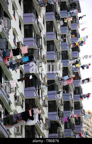 facade of the high-rise building, laundry is hanging out to dry at bars over the balcony parapet, Singapore - Stock Photo