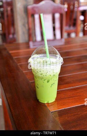 Iced green tea in plastic cup matcha green tea latte frappe and straw on table in coffee shop - Stock Photo