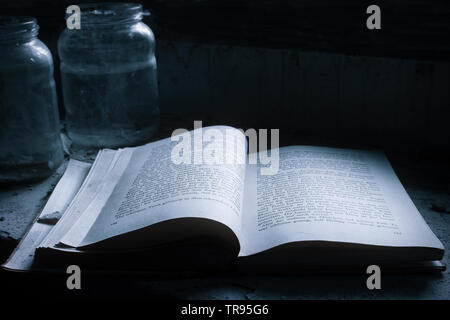 Old rare book left open and covered with dust on the table of the abandoned library - Stock Photo