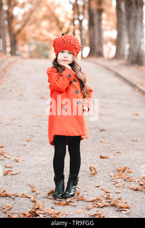 Cute stylish baby girl 4-5 year old wearing autumn jacket and knitted hat outdoors. Looking at camera. - Stock Photo