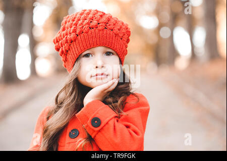 Cute baby girl 3-4 year old wearing knitted hat and jacket outdoors closeup. Looking at camera. Childhood. Autumn season. - Stock Photo