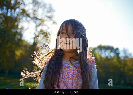 Amazing portrait of a young girl standing outside surrounded by nature looking in awe and excited whilst exploring and taking in all the beauty around - Stock Photo