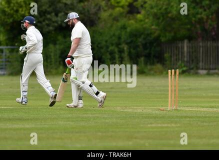 A  batsman returns to the pavilion after being bowled out in the Derbyshire and Cheshire League match between Chapel en le Frith and Pott Shrigley - Stock Photo