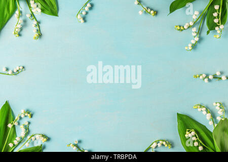 frame made of lily of the valley flowers on blue wooden table. flat lay. top view. wedding background - Stock Photo