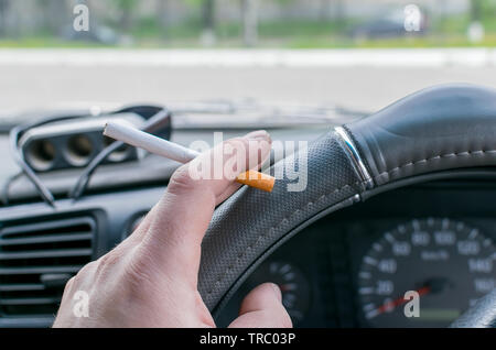 close up, in the hand of the car driver cigarette on the background of the dashboard and the street outside the window - Stock Photo