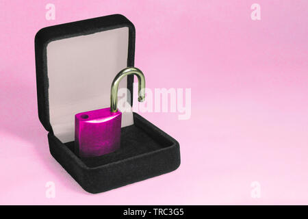 Lock in gift box. Pink padlock with open shackle in jewelry chest. Concept of security safe or protection software or hardware. Symbol of engagement o - Stock Photo