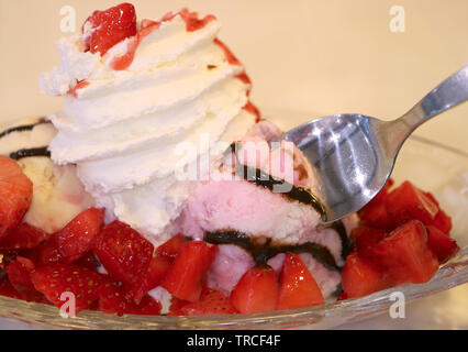 Closeup spoon scooping into strawberry ice cream topped with fresh berries and whipped cream - Stock Photo