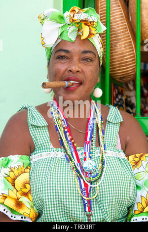 Colourfully dressed cuban lady sitting smoking a large cigar in one of the streets in the Old Town of Havana, Cuba, Caribbean - Stock Photo