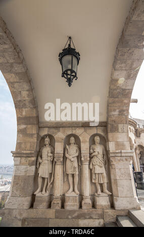 Three stone statues guarding top of stairway to Fisherman`s Bastion, in Castle district, Budapest, capital of Hungary - Stock Photo