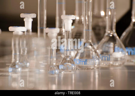 Blurry shot of serveral different flasks and beaker glasses partly filled with tranparent liquids - Stock Photo