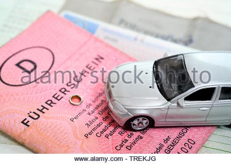 German and EU driving licenses and a model car - phased plan to renew driving license - Stock Photo